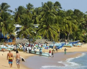 Tourists stroll whilst local fishermen work on this popular surf beach, Arugam Bay, Eastern Province, Sri Lanka, Asia